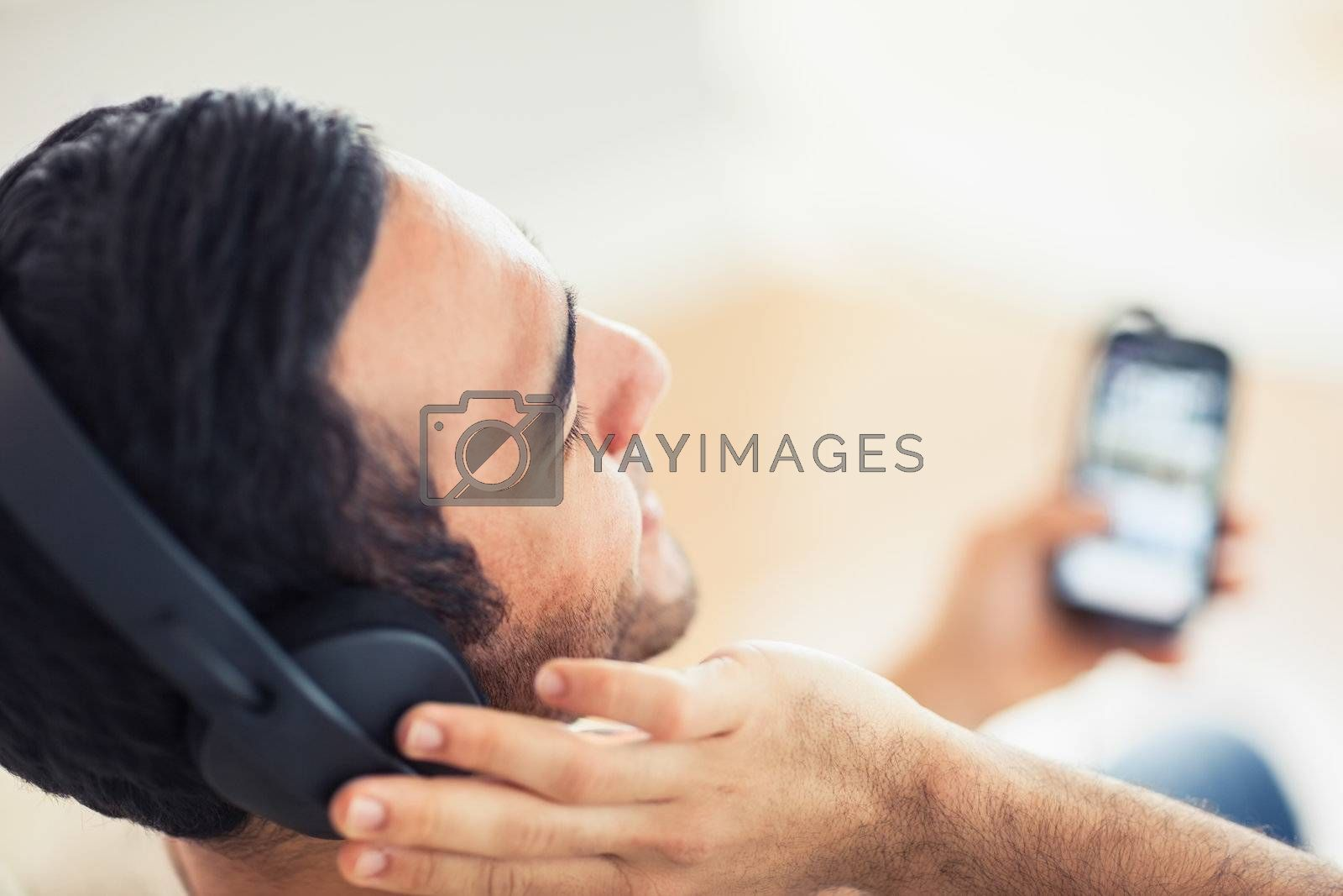 Close up on handsome man listening to music on his smartphone by Wavebreakmedia