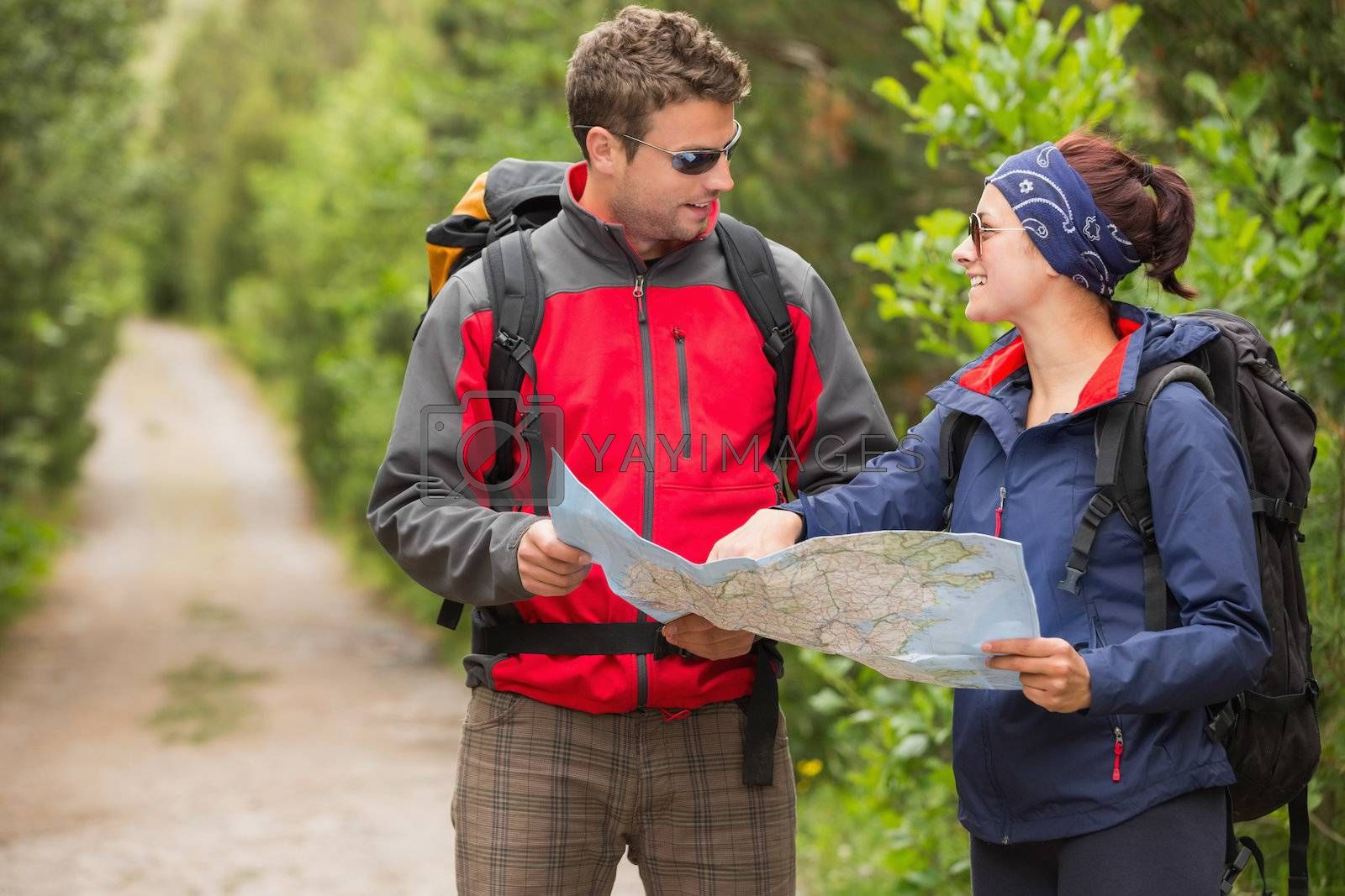 Fit couple going on a hike together looking at map by Wavebreakmedia