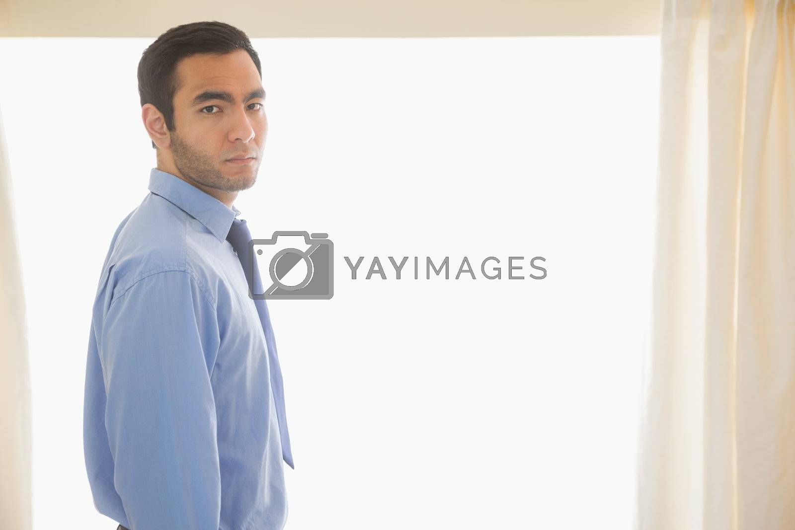 Stressed man looking standing in front of window by Wavebreakmedia