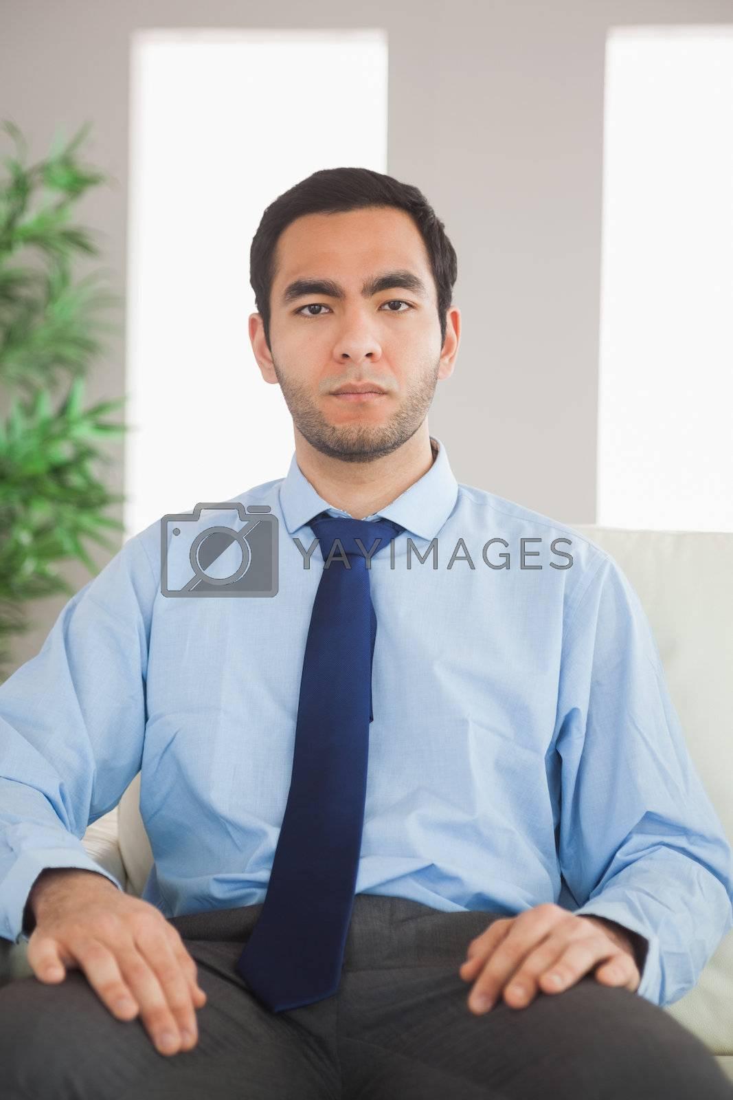 Serious classy businessman sitting on cosy sofa by Wavebreakmedia