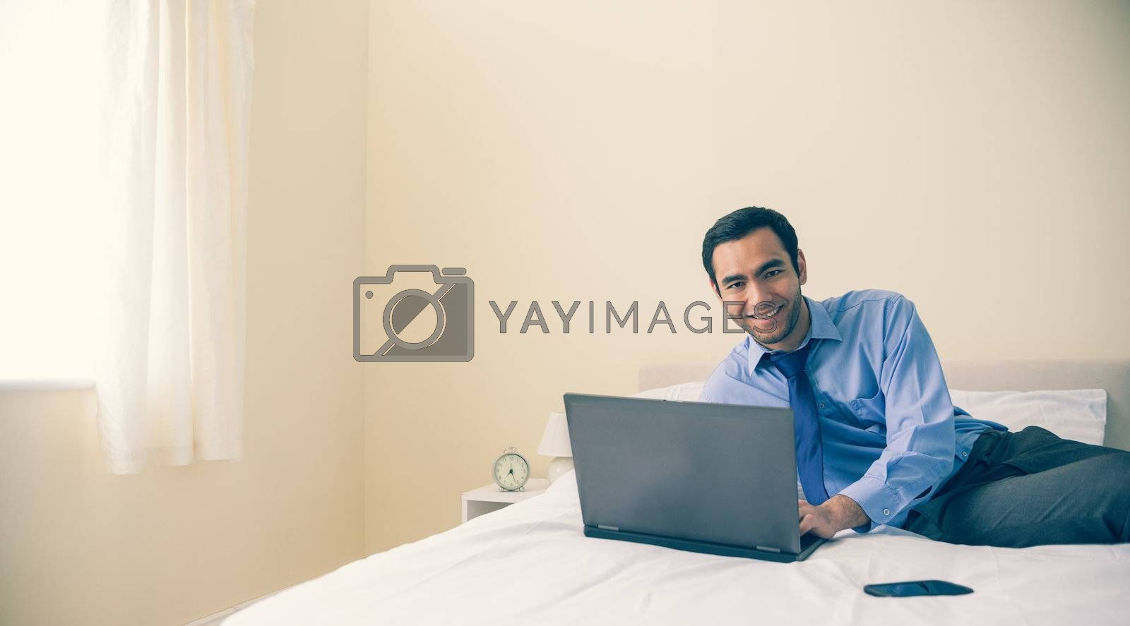 Content man lying on bed using a laptop by Wavebreakmedia