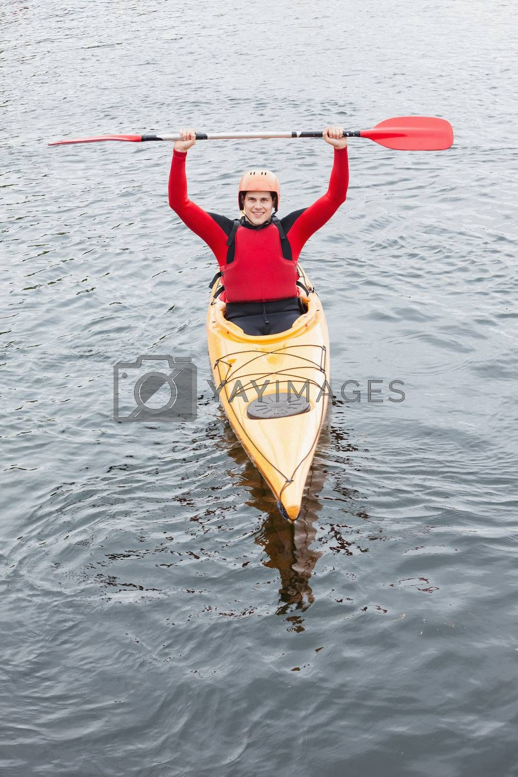 Happy man in a kayak cheering  by Wavebreakmedia
