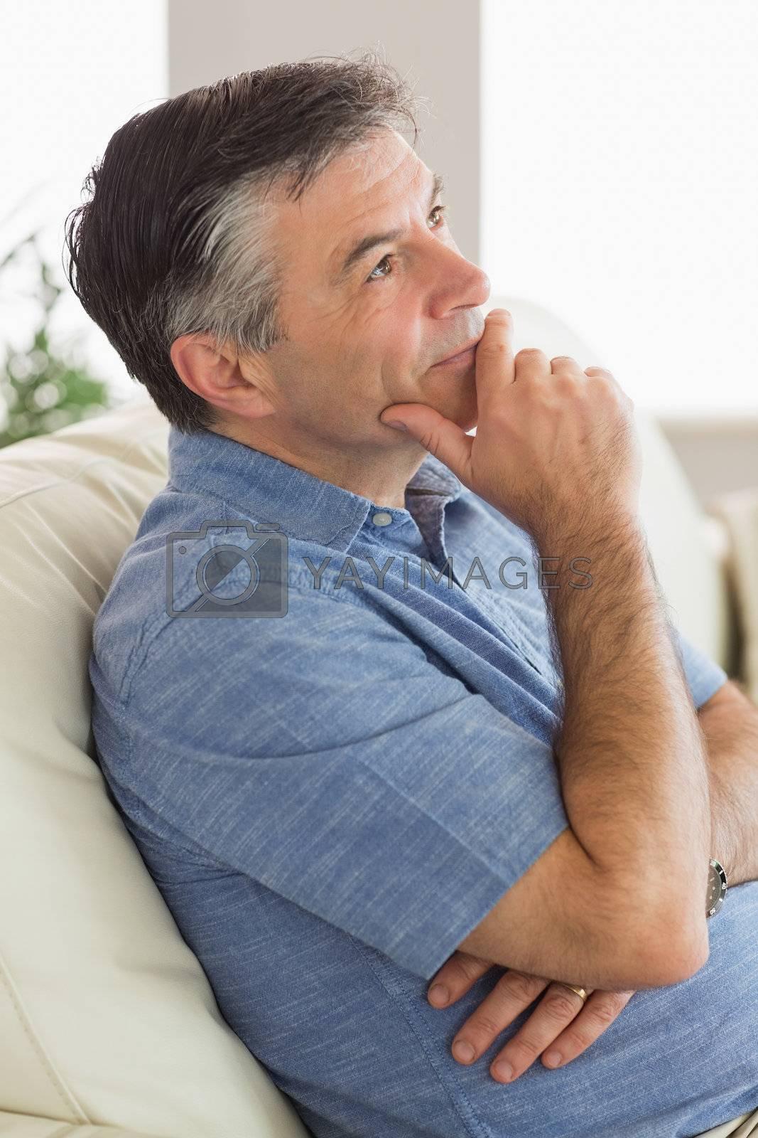 Thinking man sitting on sofa by Wavebreakmedia