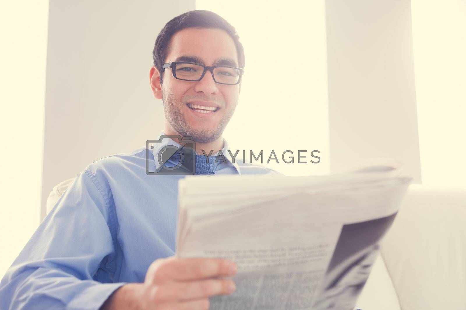 Happy man looking at camera and holding a newspaper by Wavebreakmedia
