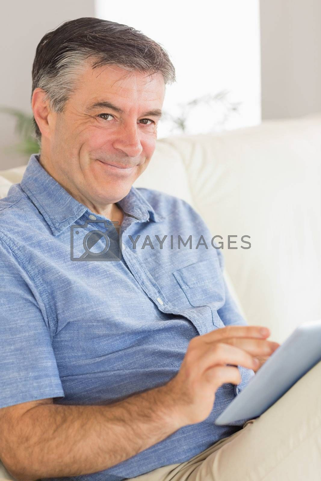 Smiling man sitting on a sofa using a tablet pc by Wavebreakmedia