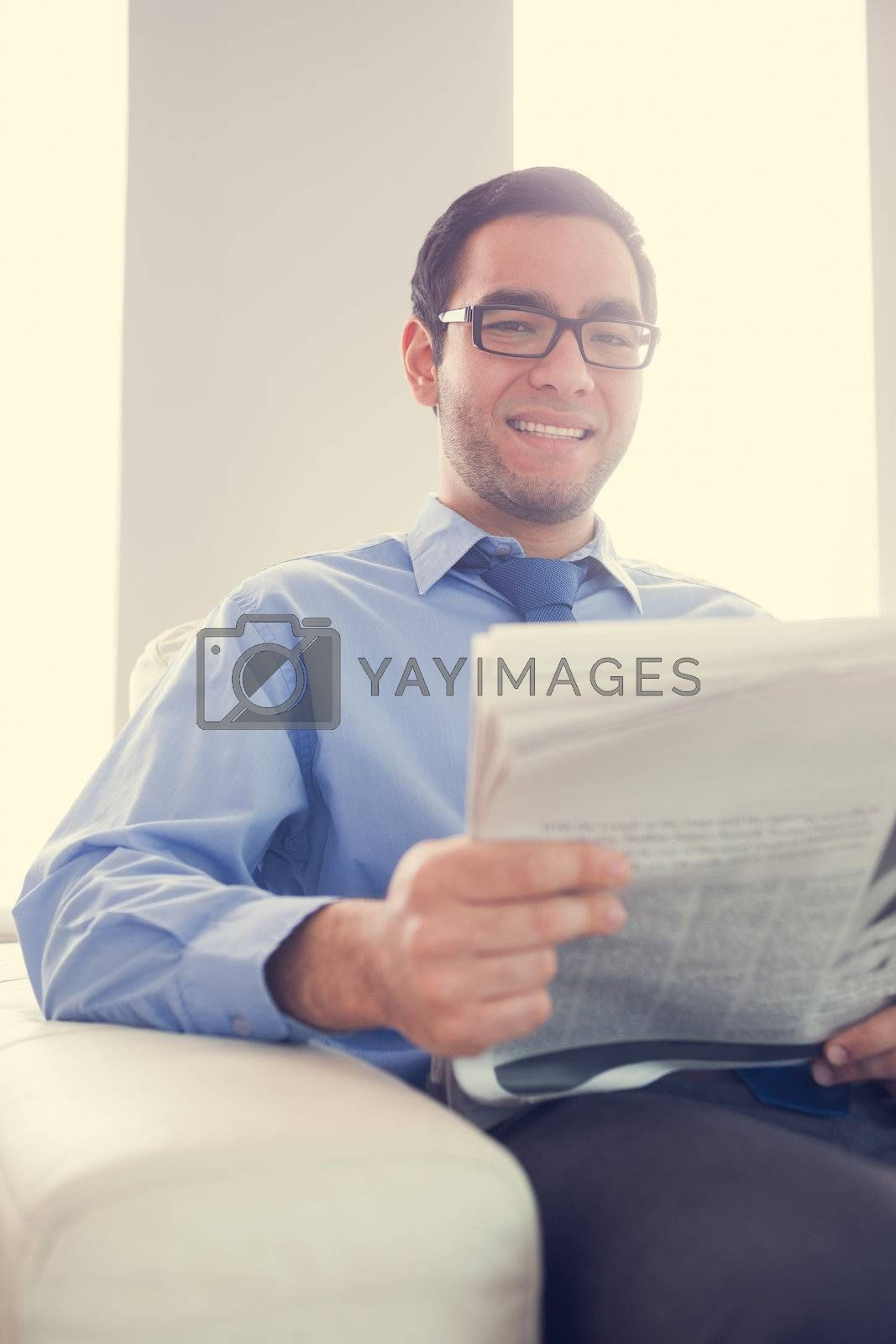 Content man looking and holding a newspaper sitting on sofa by Wavebreakmedia