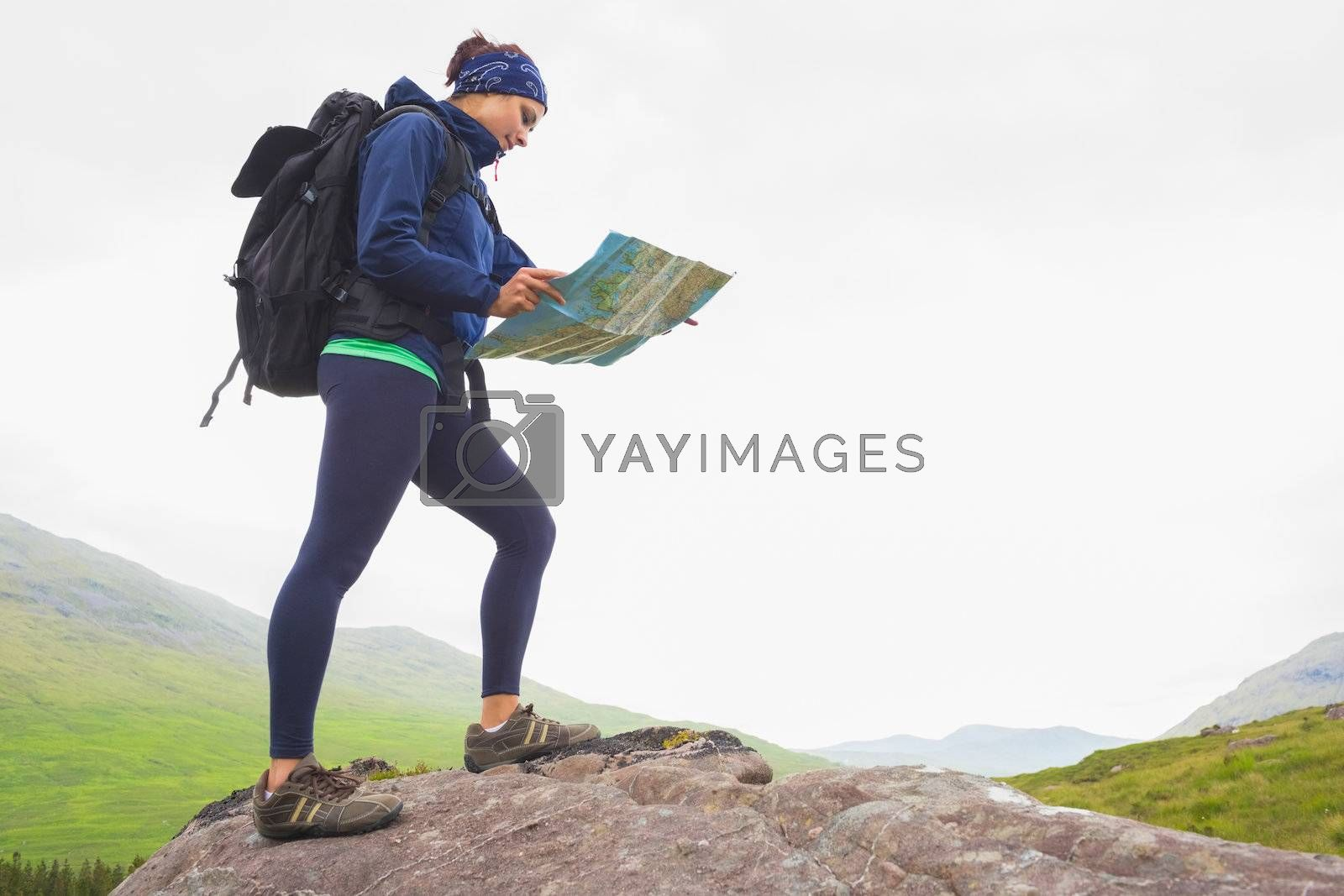 Woman standing on a rock reading map by Wavebreakmedia