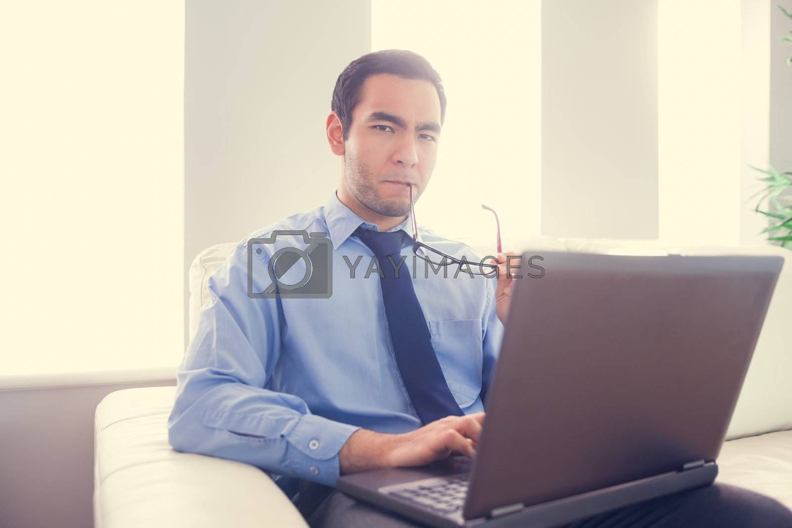 Nervous man biting his eyeglasses and using a laptop by Wavebreakmedia