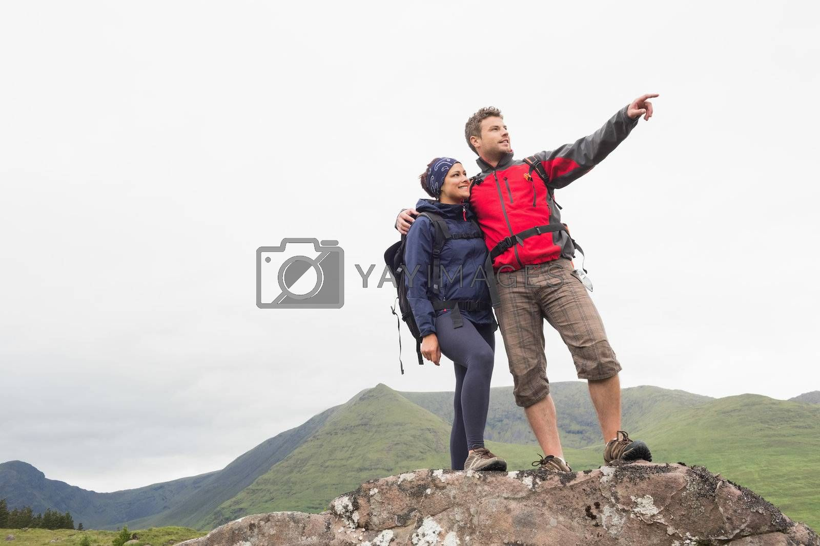 Couple standing on a rock looking at the mountains by Wavebreakmedia