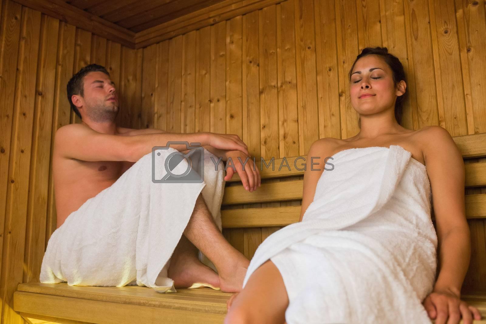 Happy couple relaxing in a sauna by Wavebreakmedia