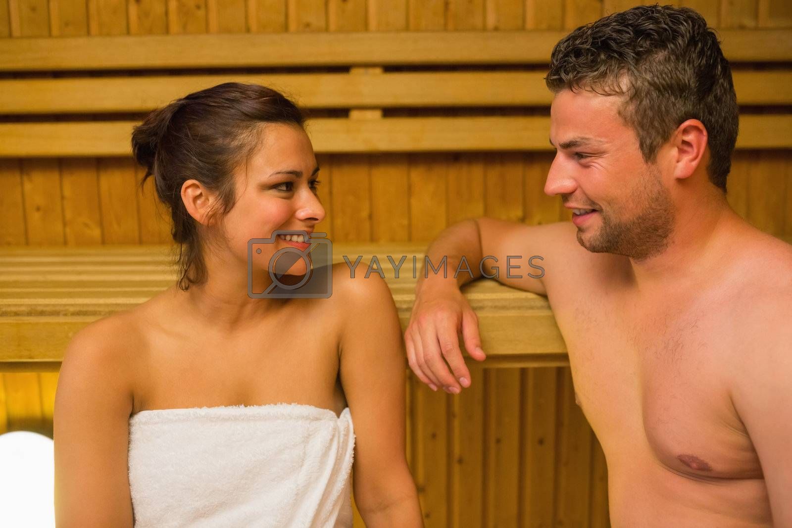 Smiling couple relaxing in a sauna and chatting by Wavebreakmedia