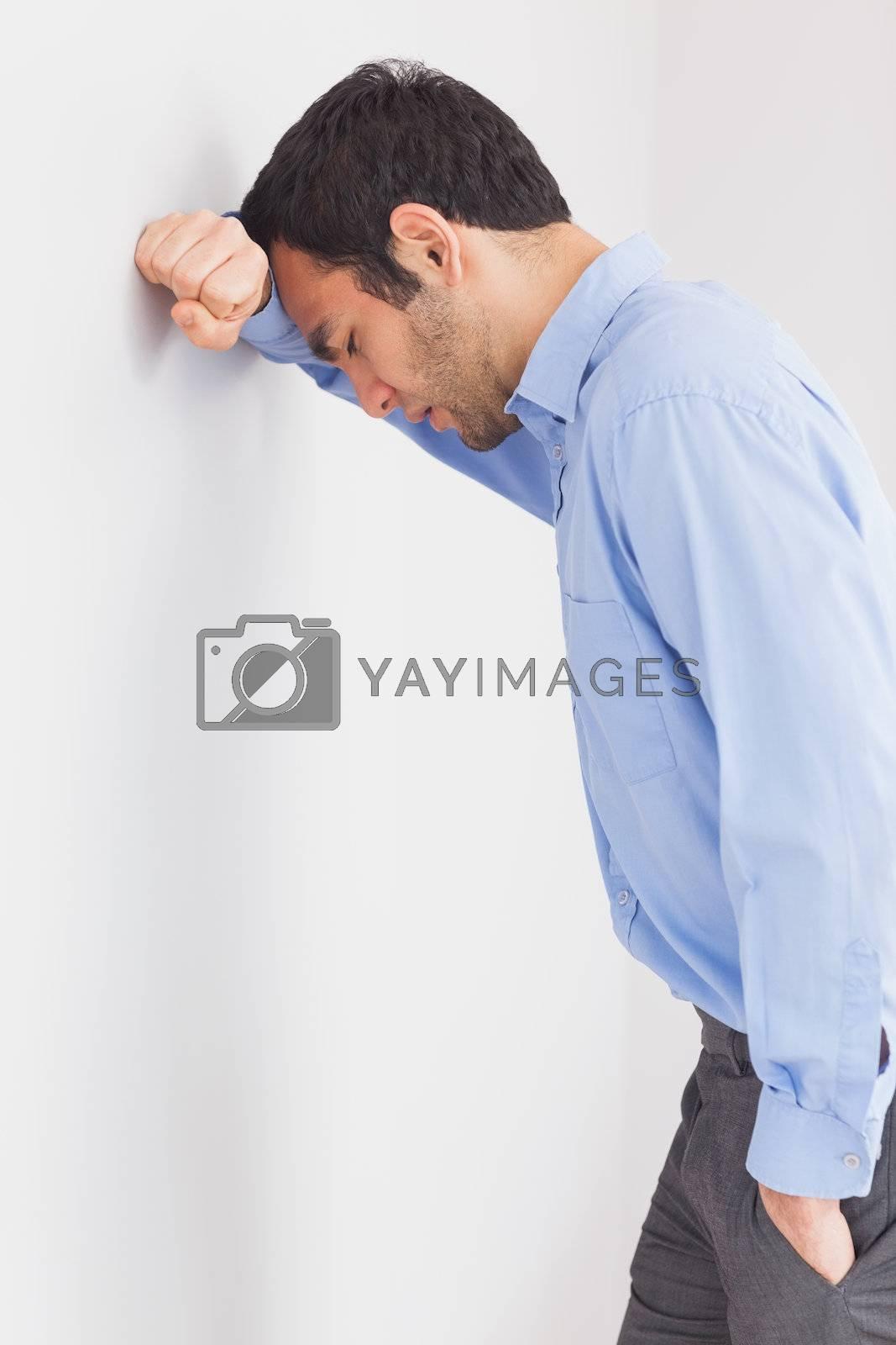 Worried man leaning his head against a wall by Wavebreakmedia