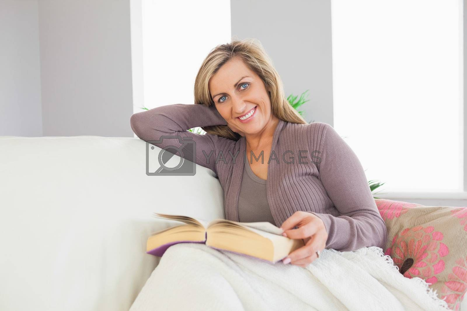 Smiling woman holding a book and lying on a sofa by Wavebreakmedia