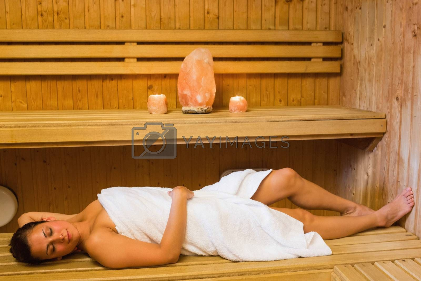 Happy brunette woman lying in a sauna by Wavebreakmedia