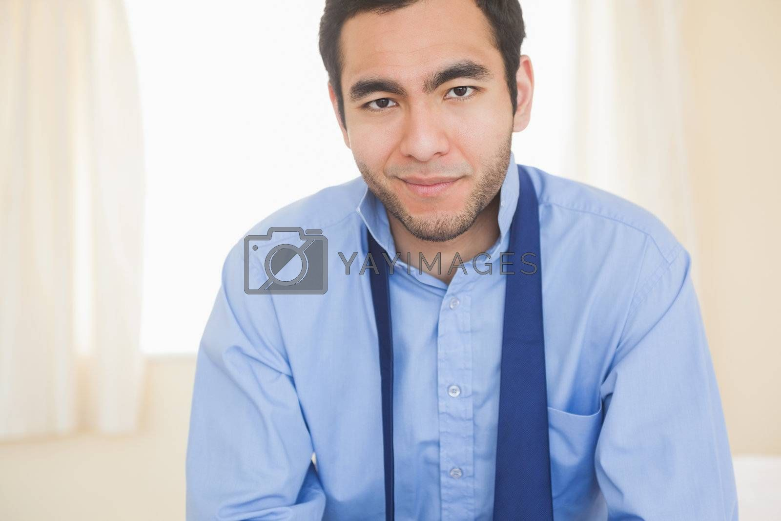 Relaxed man smiling at camera sitting on a bed by Wavebreakmedia