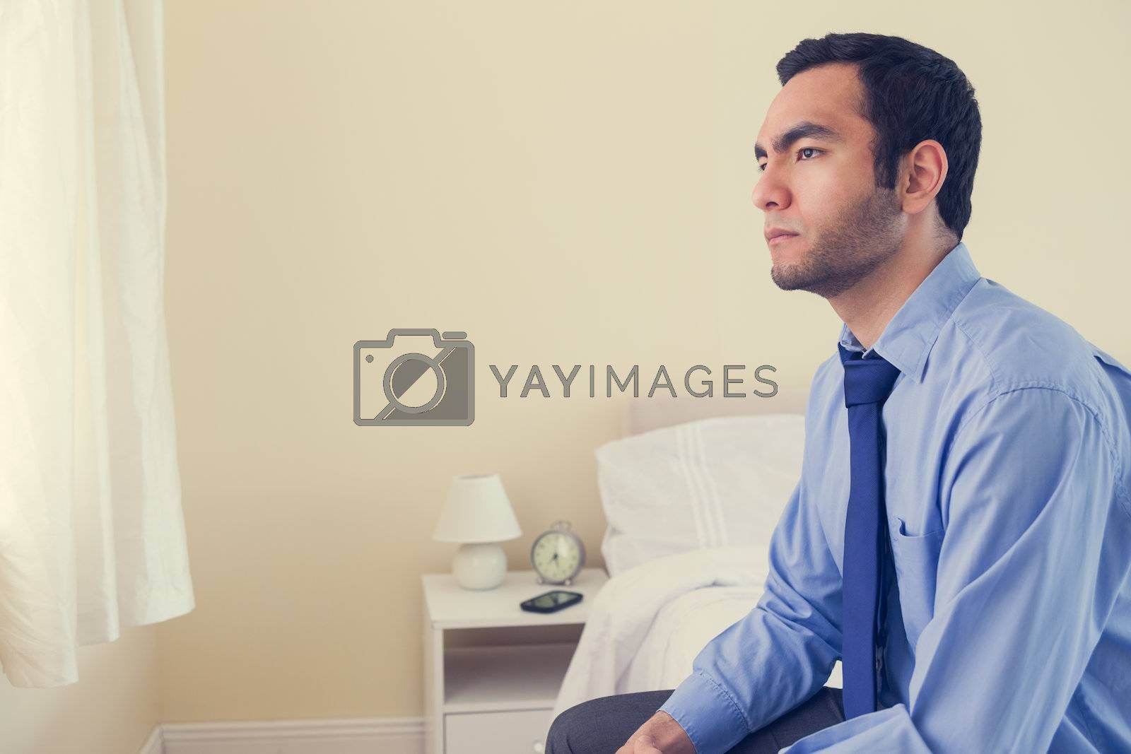 Unhappy man looking away sitting on his bed by Wavebreakmedia