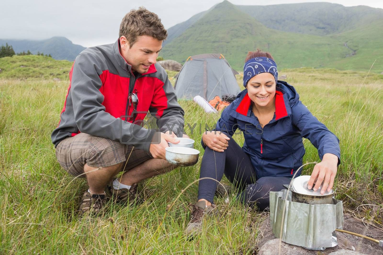 Couple cooking outside on camping trip by Wavebreakmedia