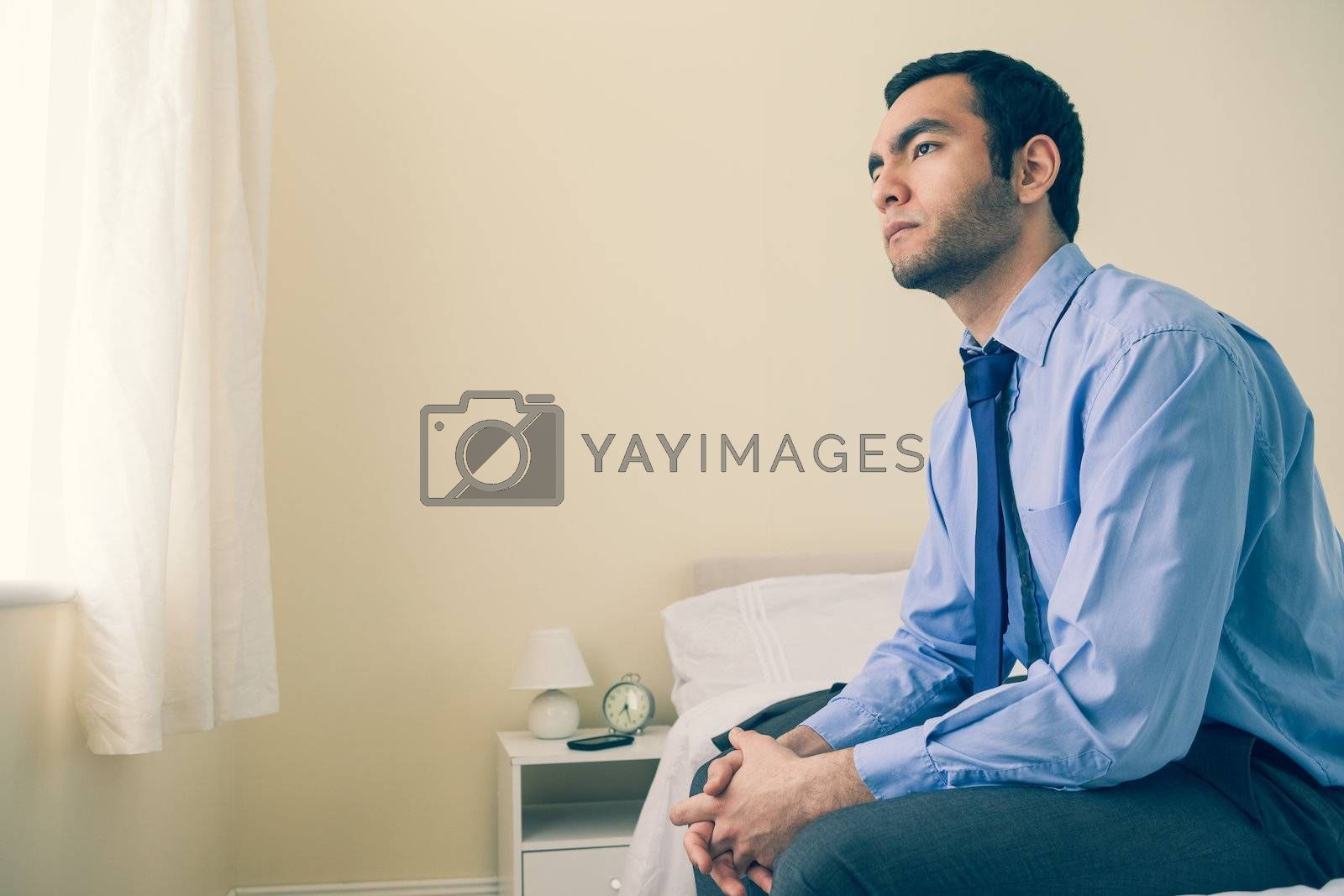 Thinking man looking away sitting on his bed by Wavebreakmedia