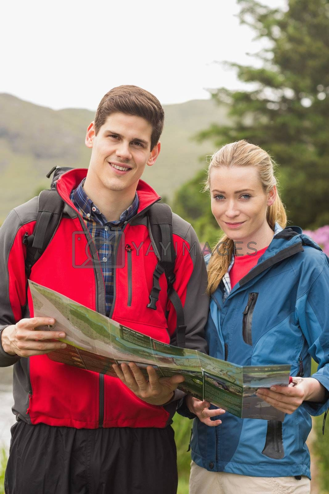 Happy couple holding map on a hike by Wavebreakmedia
