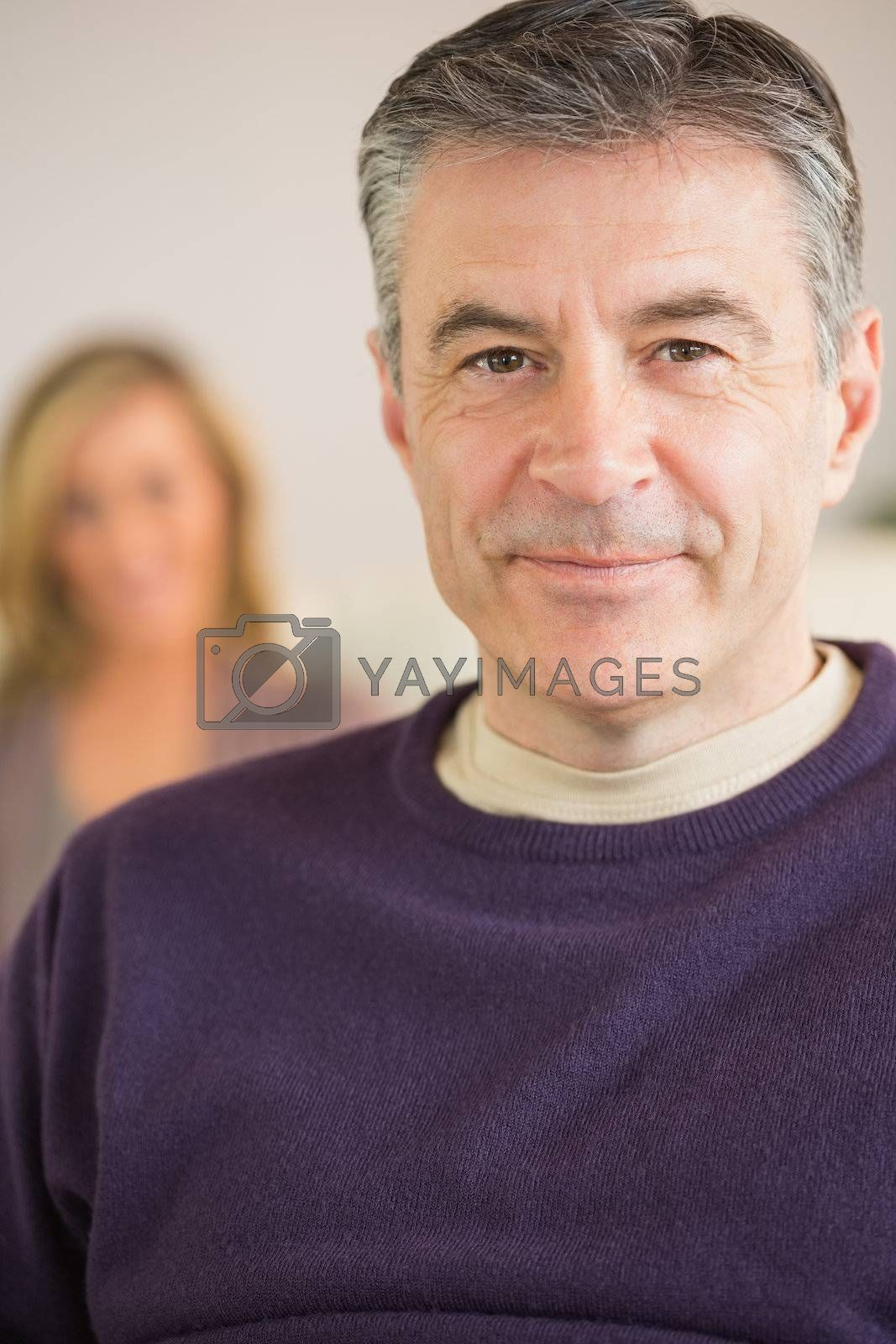 Smiling man with his wife in the background by Wavebreakmedia