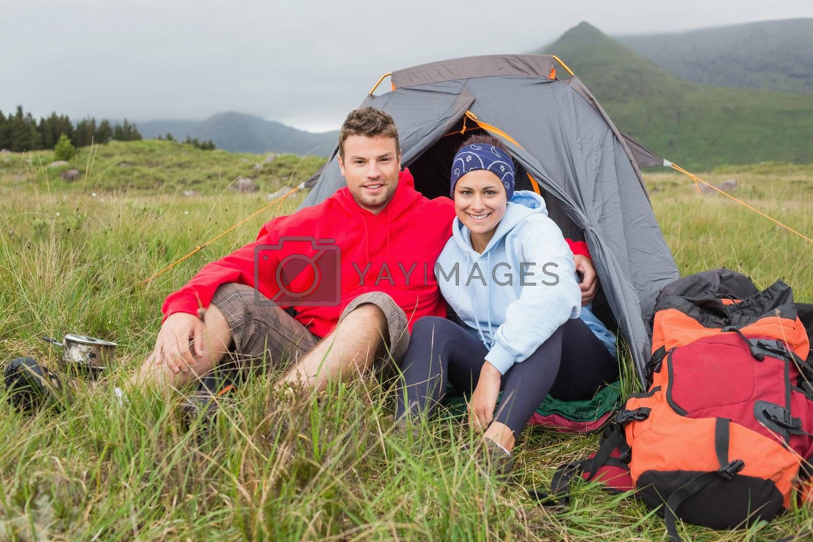 Couple on camping trip smiling at camera by Wavebreakmedia