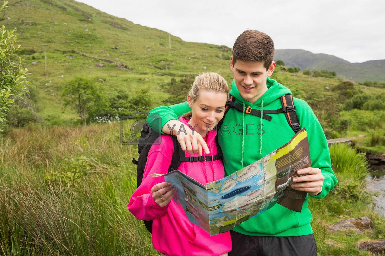 Athletic couple in hooded jumpers on hike reading map by Wavebreakmedia