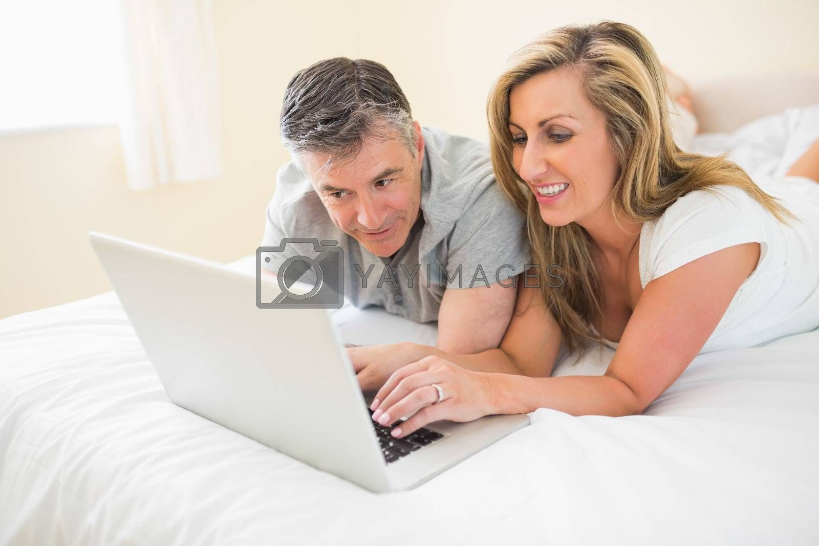 Happy couple lying on a bed watching a laptop by Wavebreakmedia