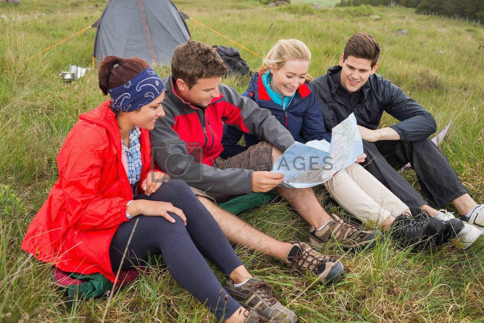 Friends sitting down looking at map on camping trip by Wavebreakmedia