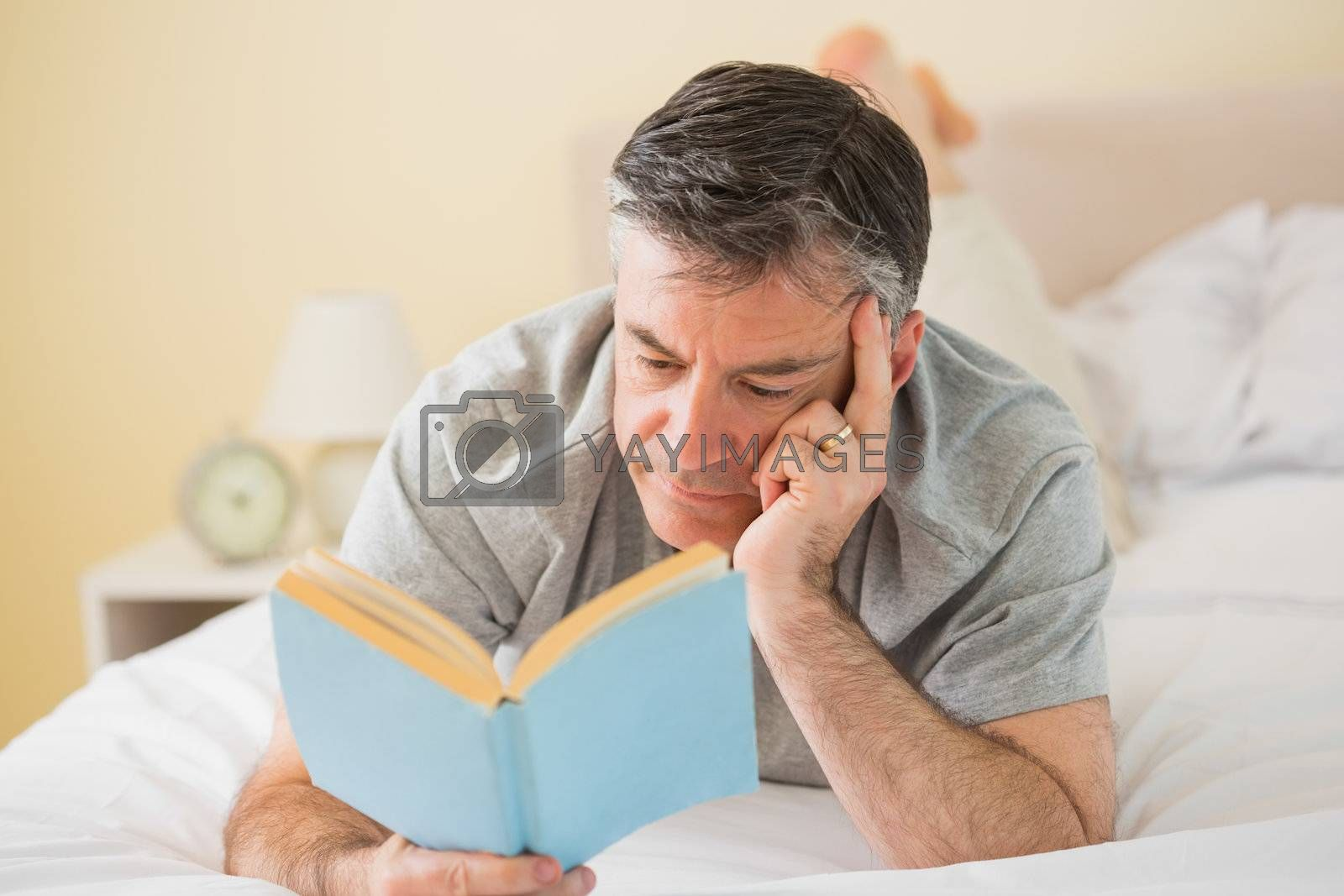 Concentrated man reading a book on his bed by Wavebreakmedia