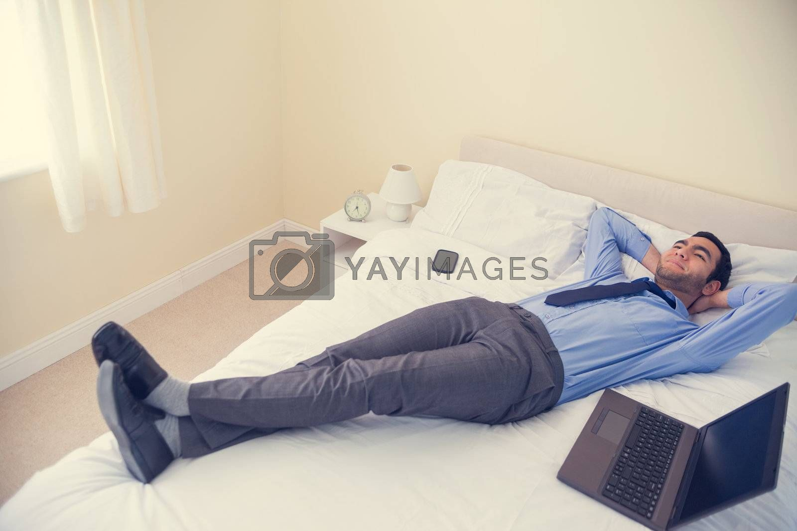 Pleased man relaxing on his bed by Wavebreakmedia