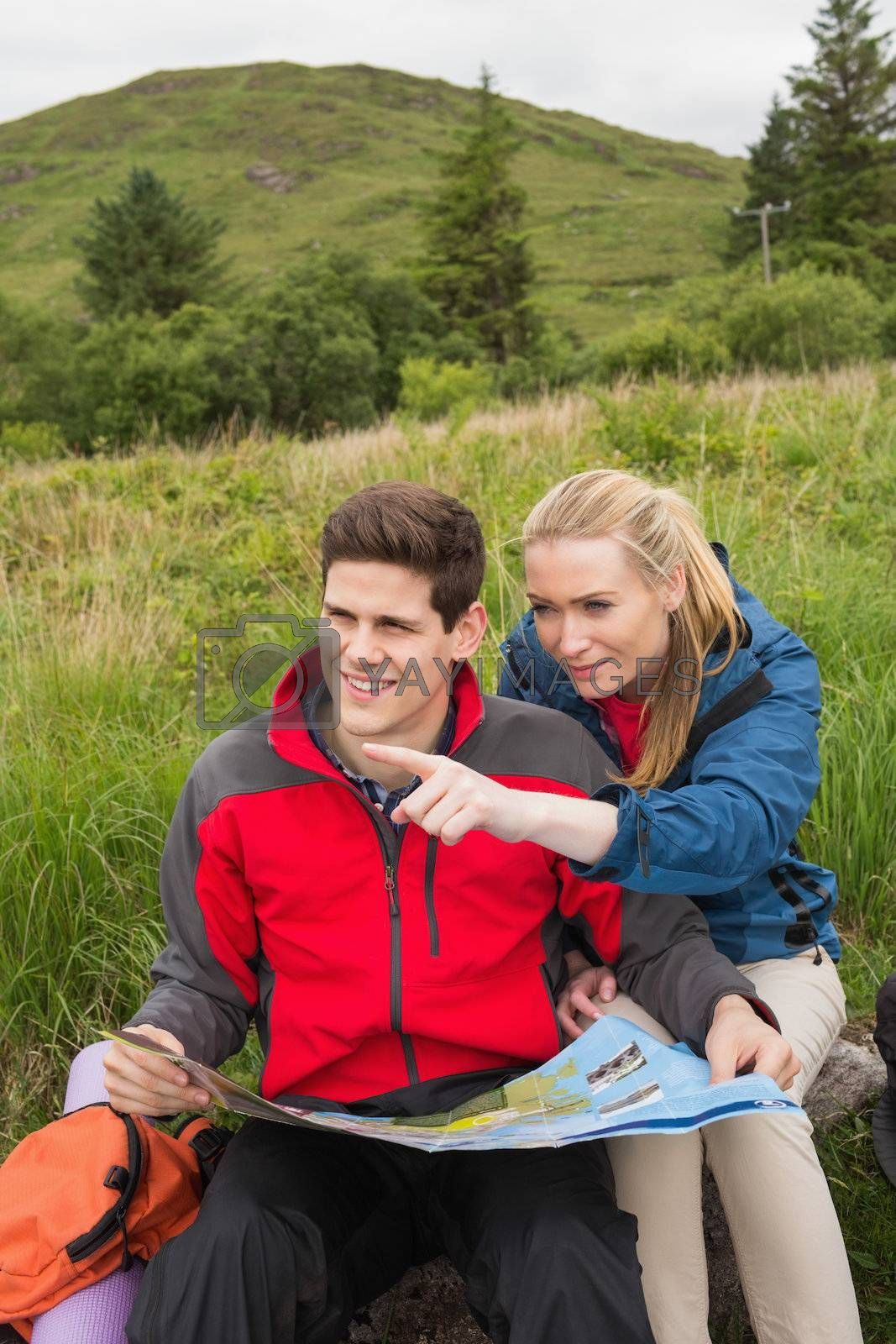 Cheerful couple taking a break on a hike to look at map with woman pointing by Wavebreakmedia