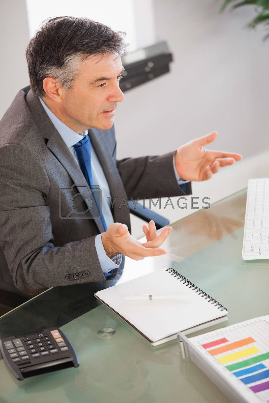 A businessman sitting at his desk explaining something  by Wavebreakmedia