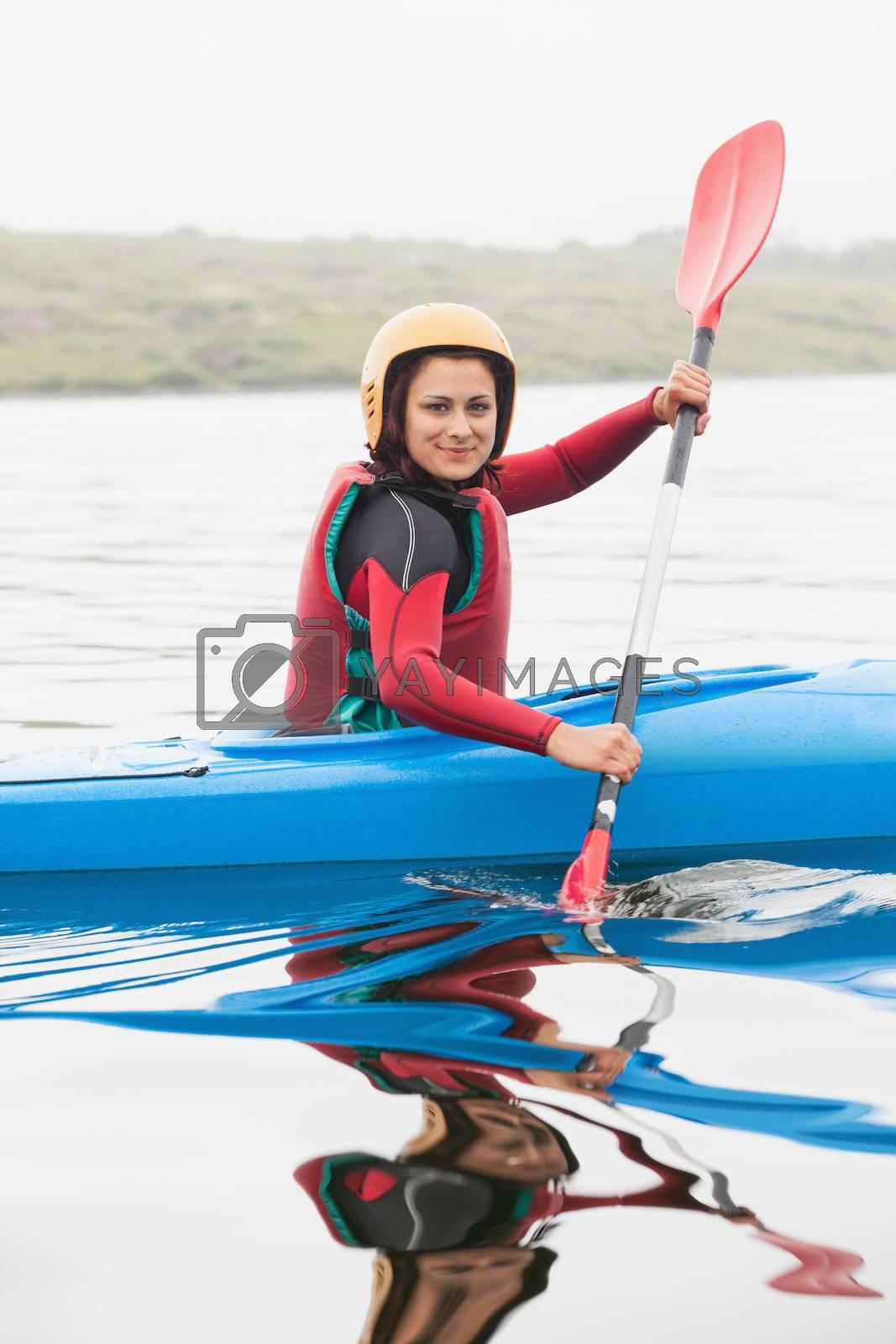 Happy woman rowing on lake by Wavebreakmedia