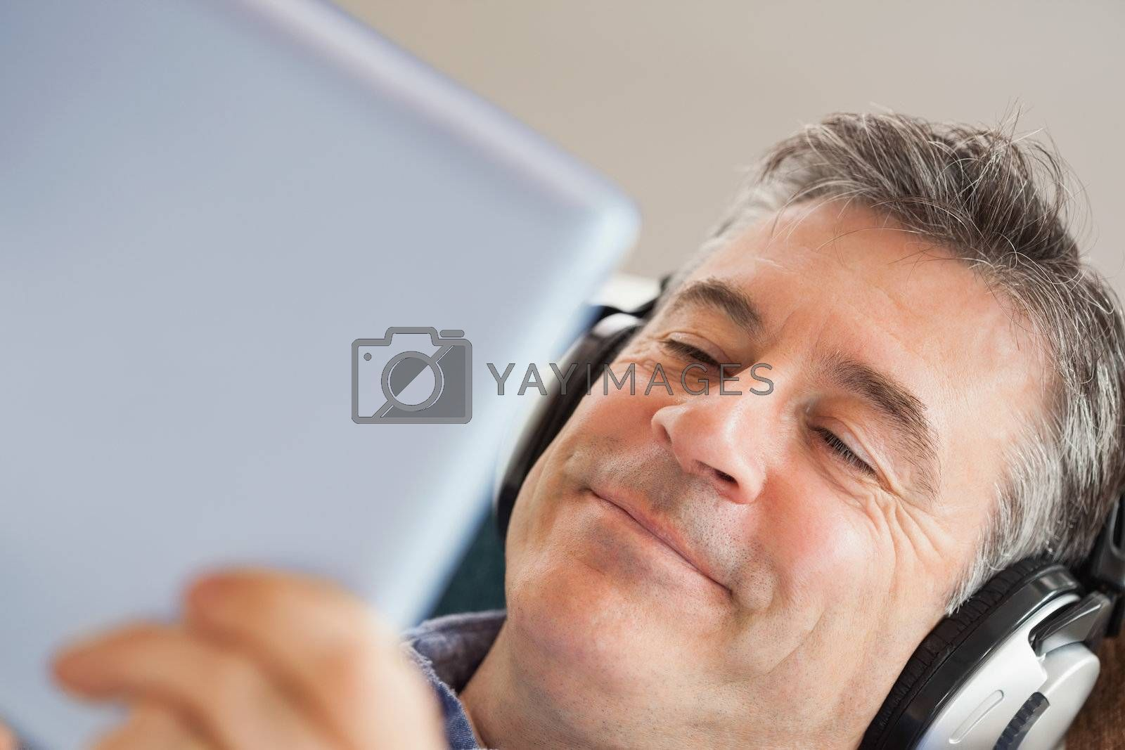 Smiling man listening music and using a tablet pc by Wavebreakmedia