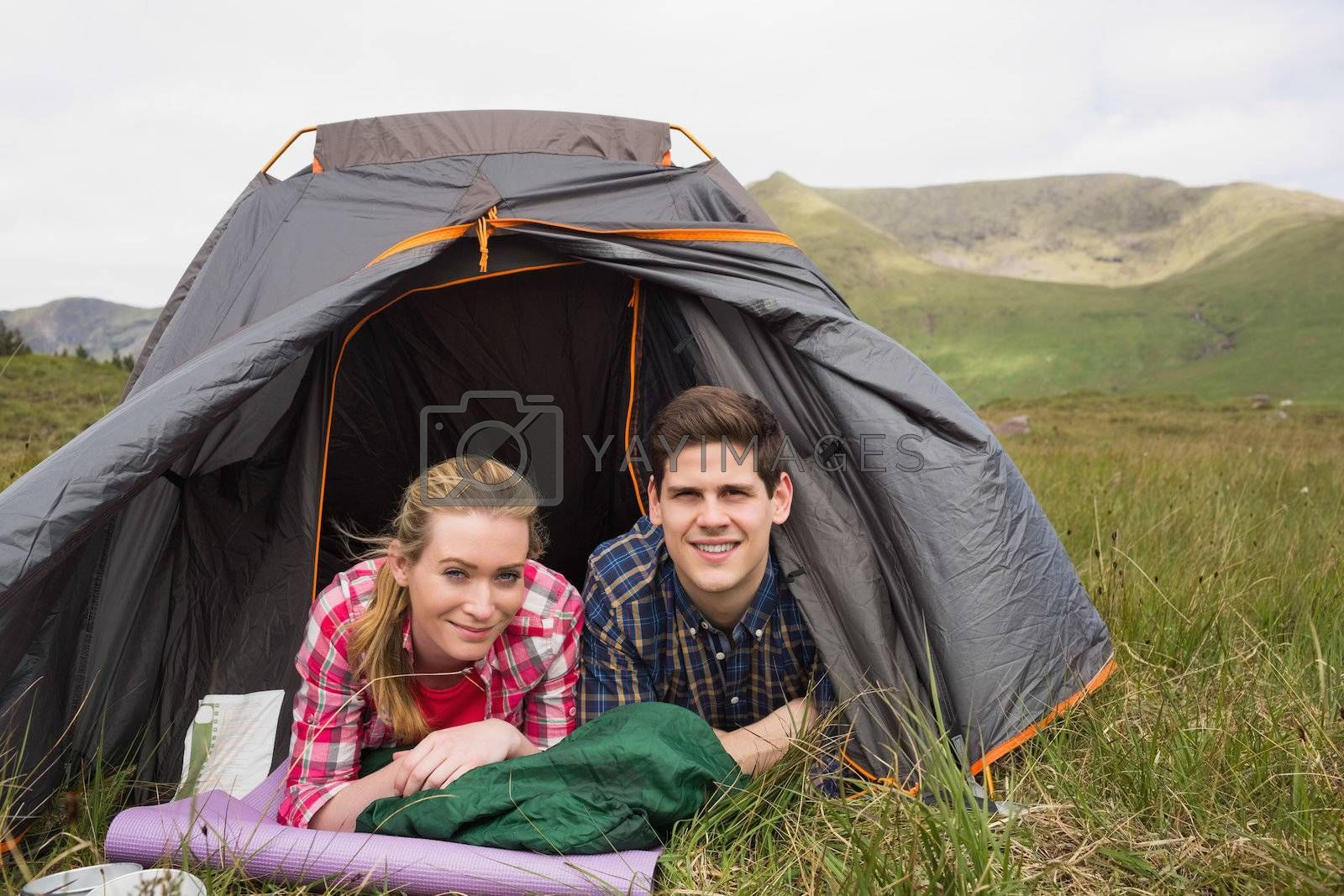 Happy couple lying in their tent after a hike and looking at camera by Wavebreakmedia