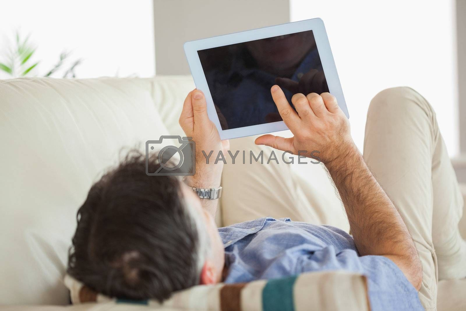 Man laying on sofa using a tablet pc by Wavebreakmedia