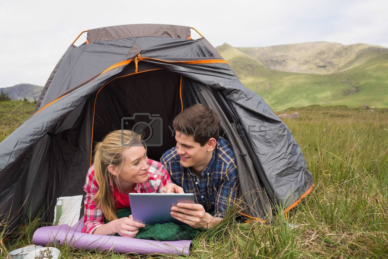 Happy couple lying in their tent and using digital tablet by Wavebreakmedia