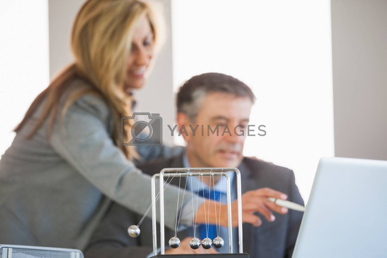 Colleagues discussing in an office with a newtons cradle in the foreground by Wavebreakmedia
