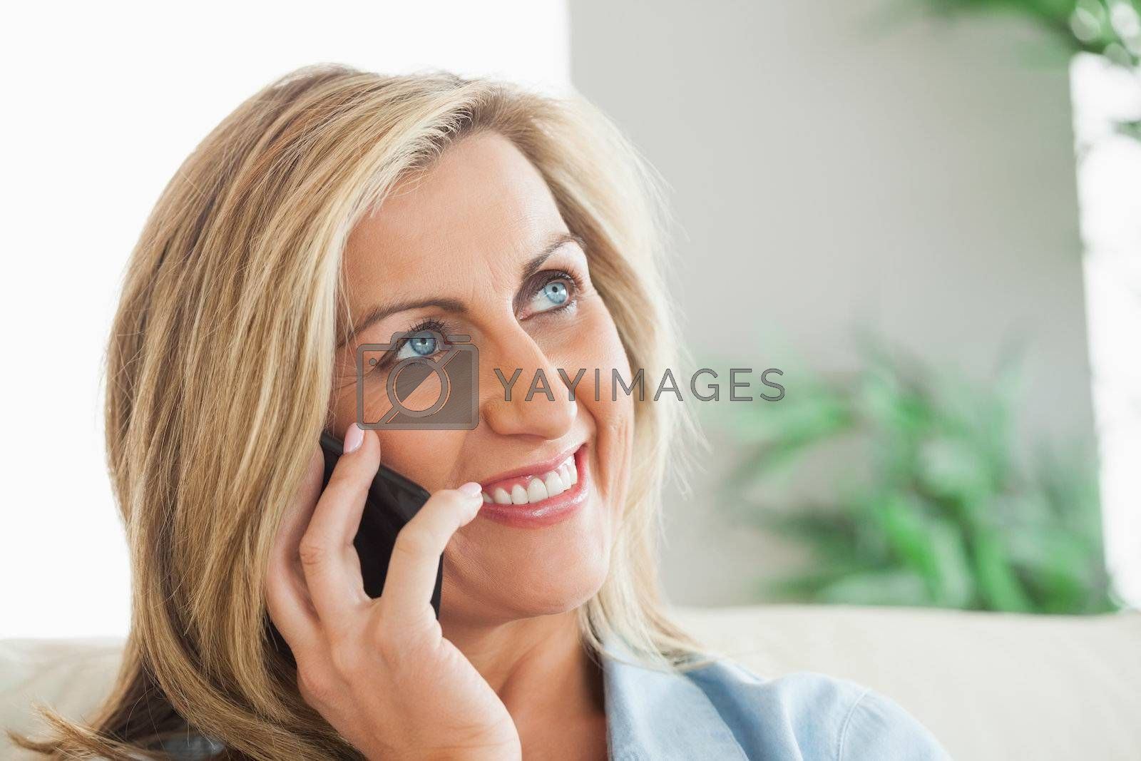 Smiling woman calling someone with her mobile phone by Wavebreakmedia