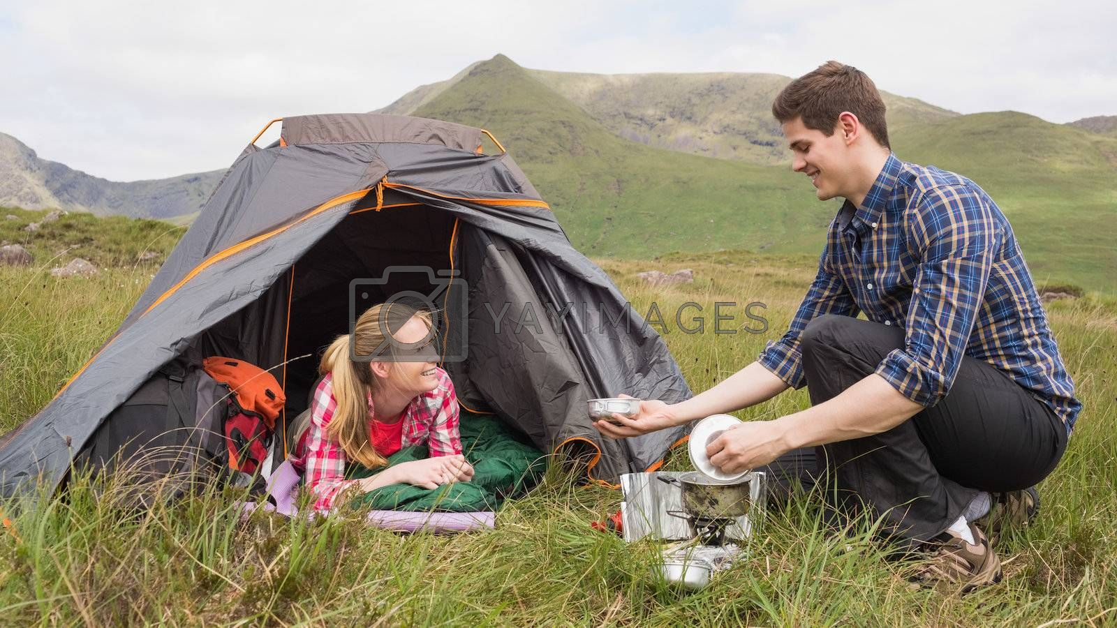 Smiling couple cooking outside on camping trip by Wavebreakmedia
