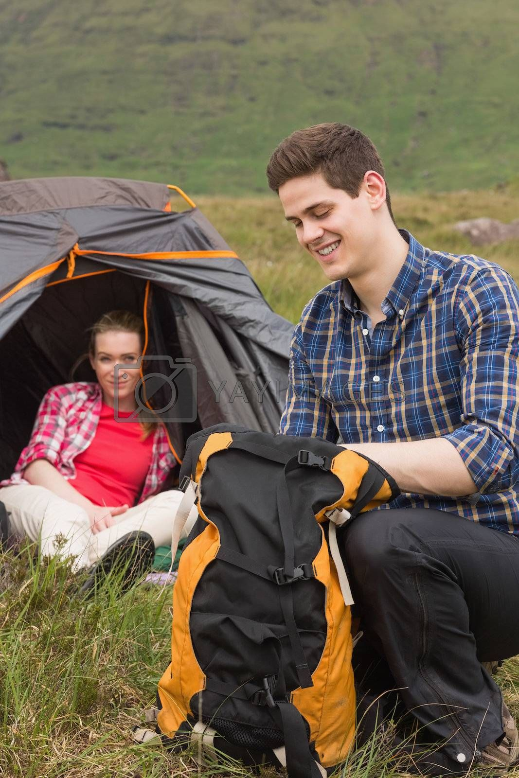 Man packing backpack while girlfriend sits in tent by Wavebreakmedia
