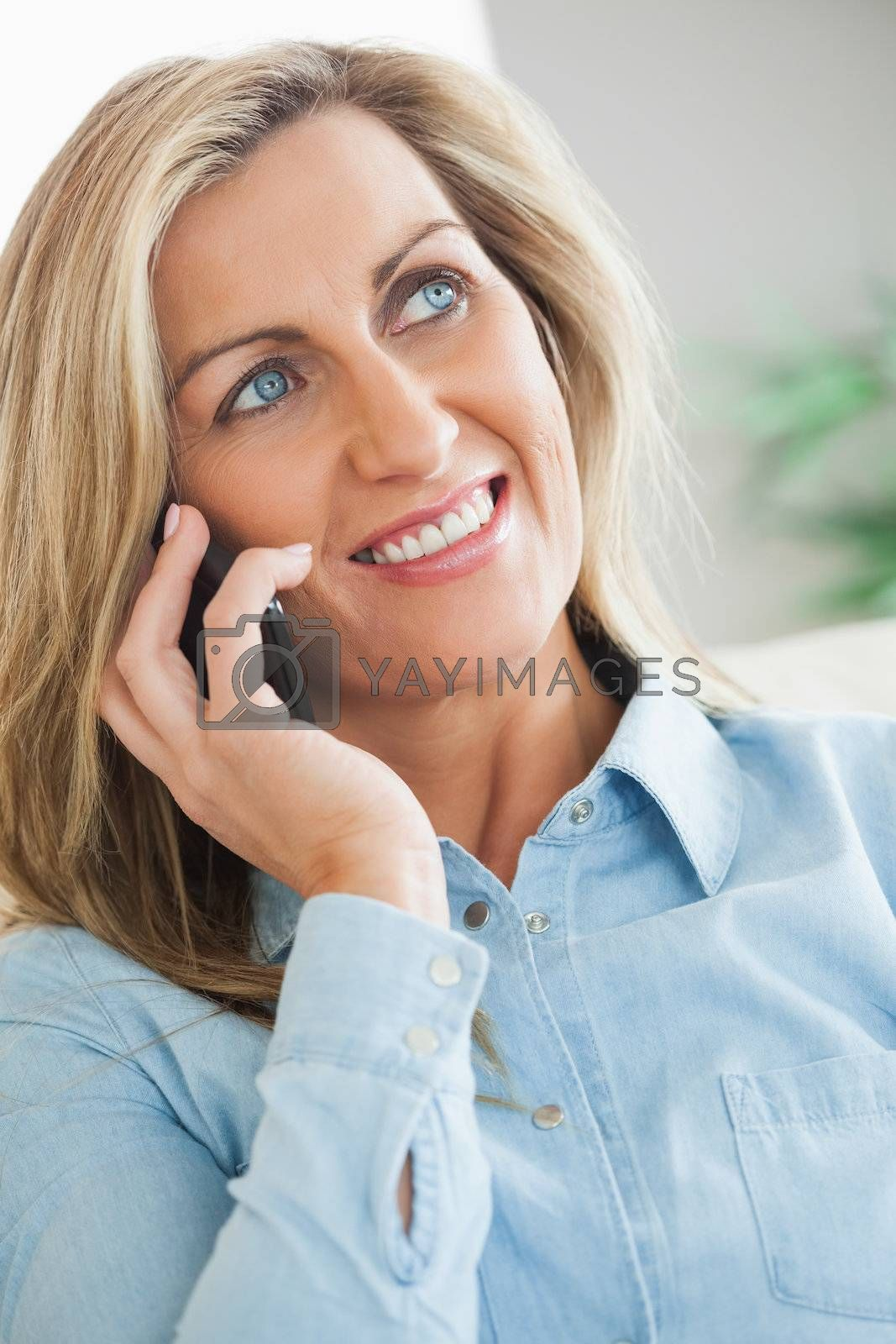 Smiling woman calling someome with her mobile phone by Wavebreakmedia