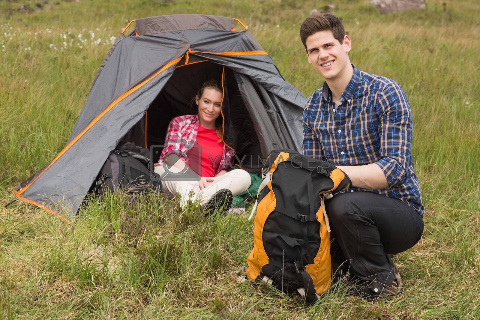 Smiling man packing backpack while girlfriend sits in tent by Wavebreakmedia
