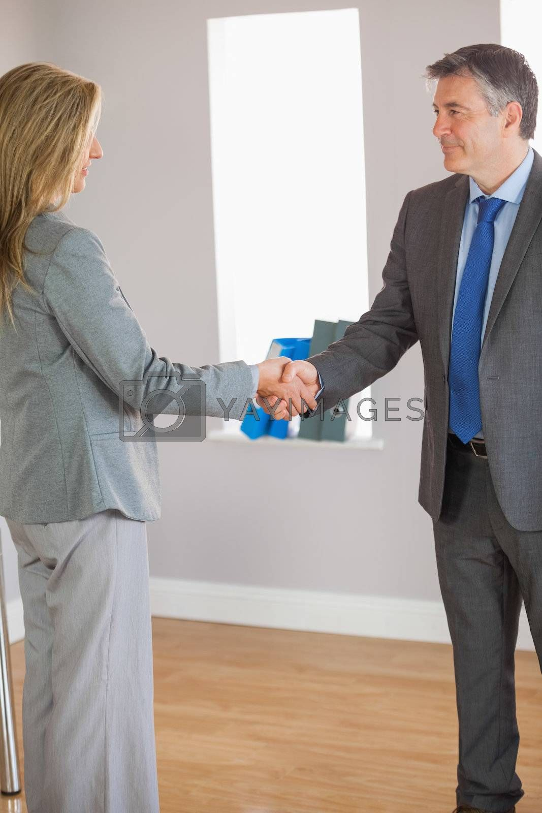 Business team shaking hands and smiling by Wavebreakmedia