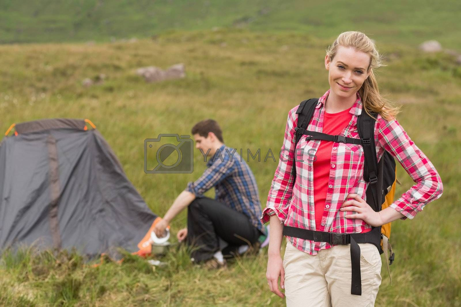 Cheerful woman carrying backpack while boyfriend is pitching tent by Wavebreakmedia