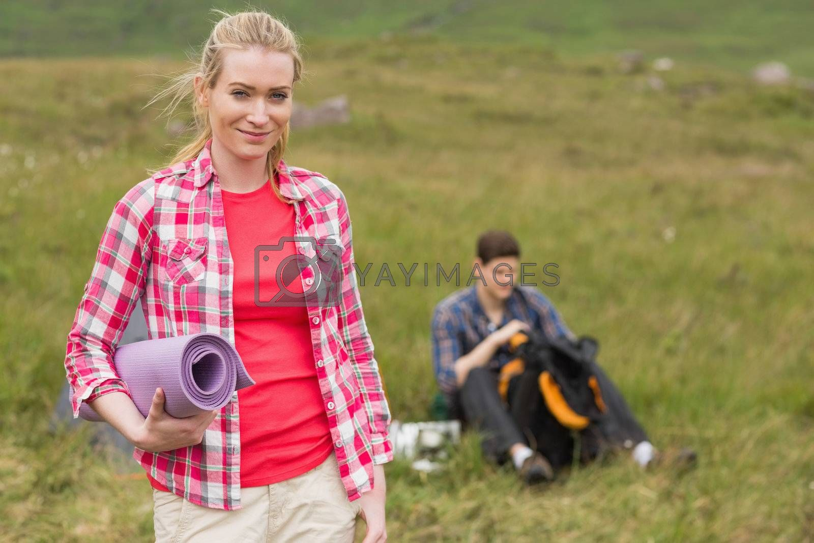 Happy woman carrying camping mat by Wavebreakmedia