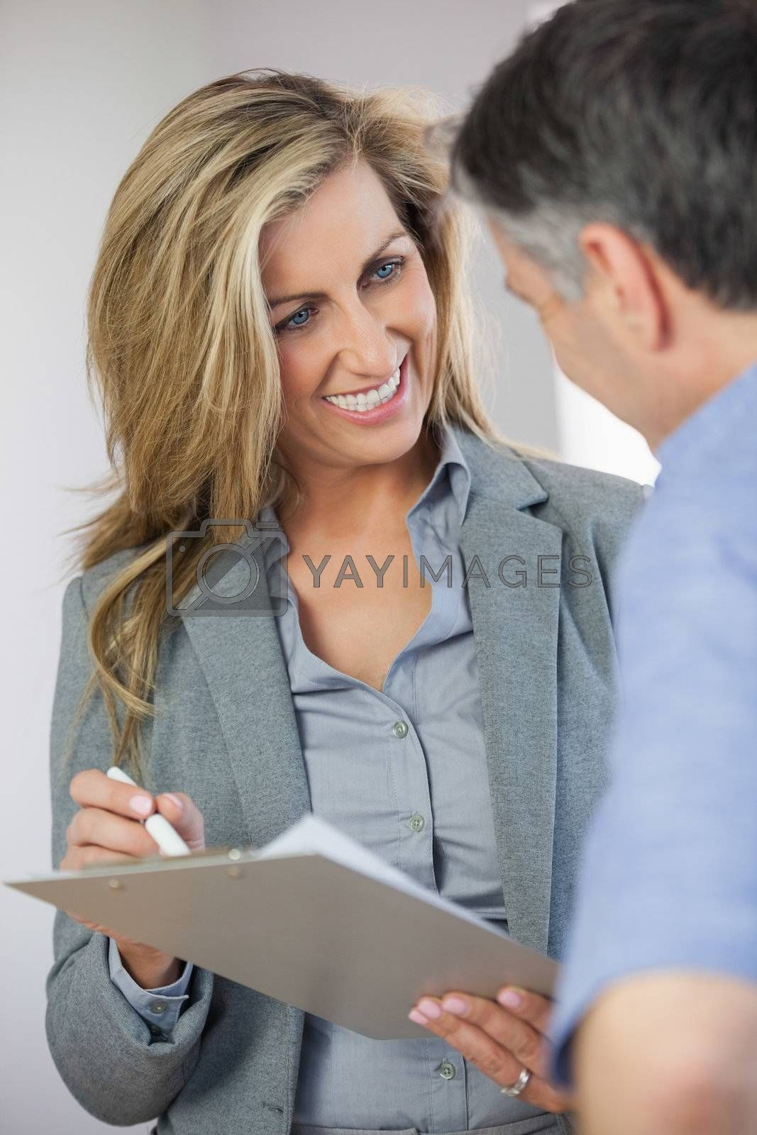 Estate agent showing lease to customer and smiling by Wavebreakmedia