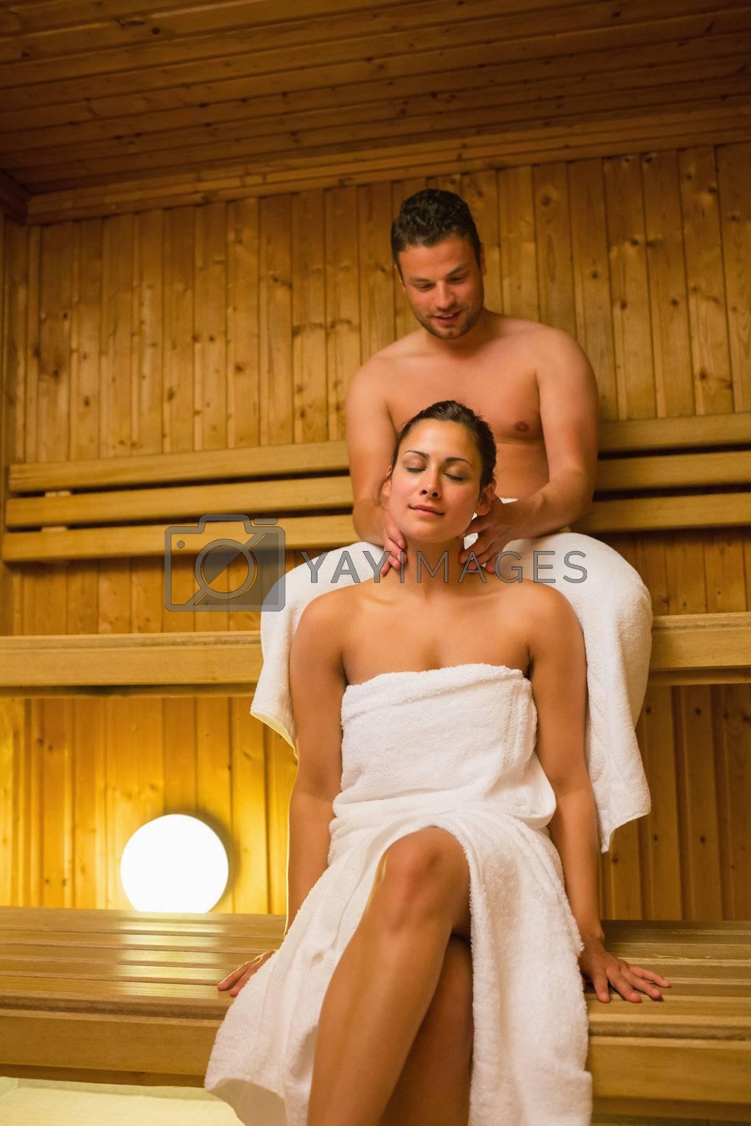 Man giving his girlfriend a neck massage in sauna by Wavebreakmedia