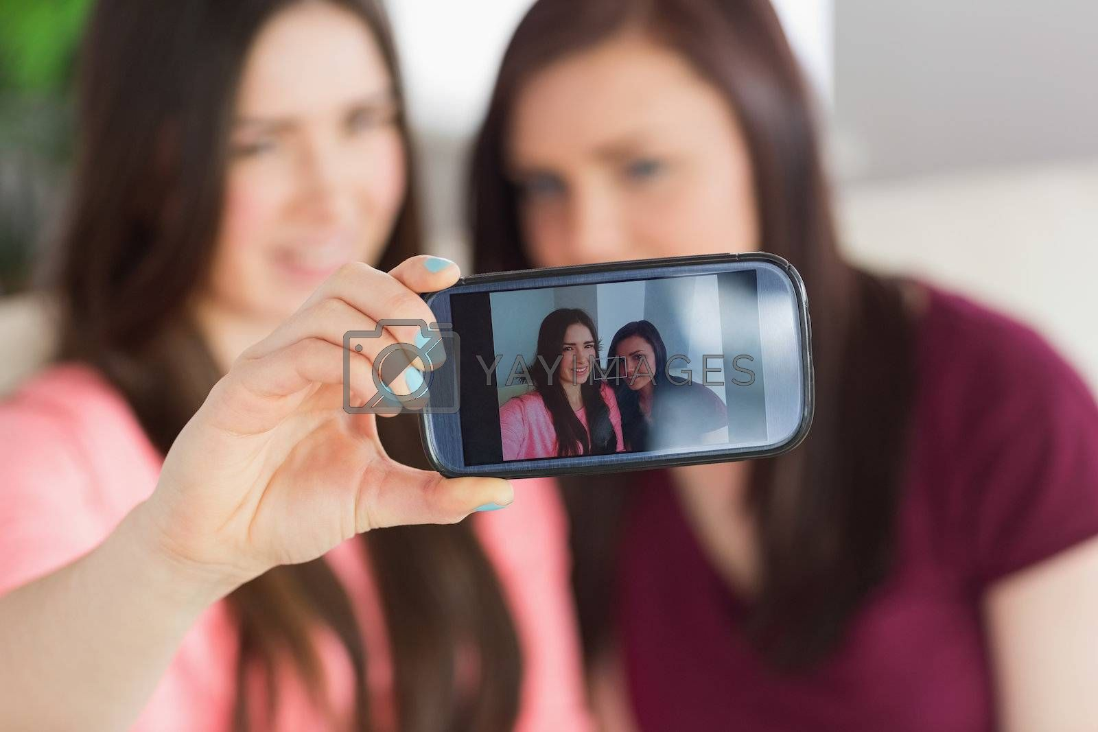 Two smiling girls sitting on a sofa taking a photo of themselves with a mobile phone by Wavebreakmedia