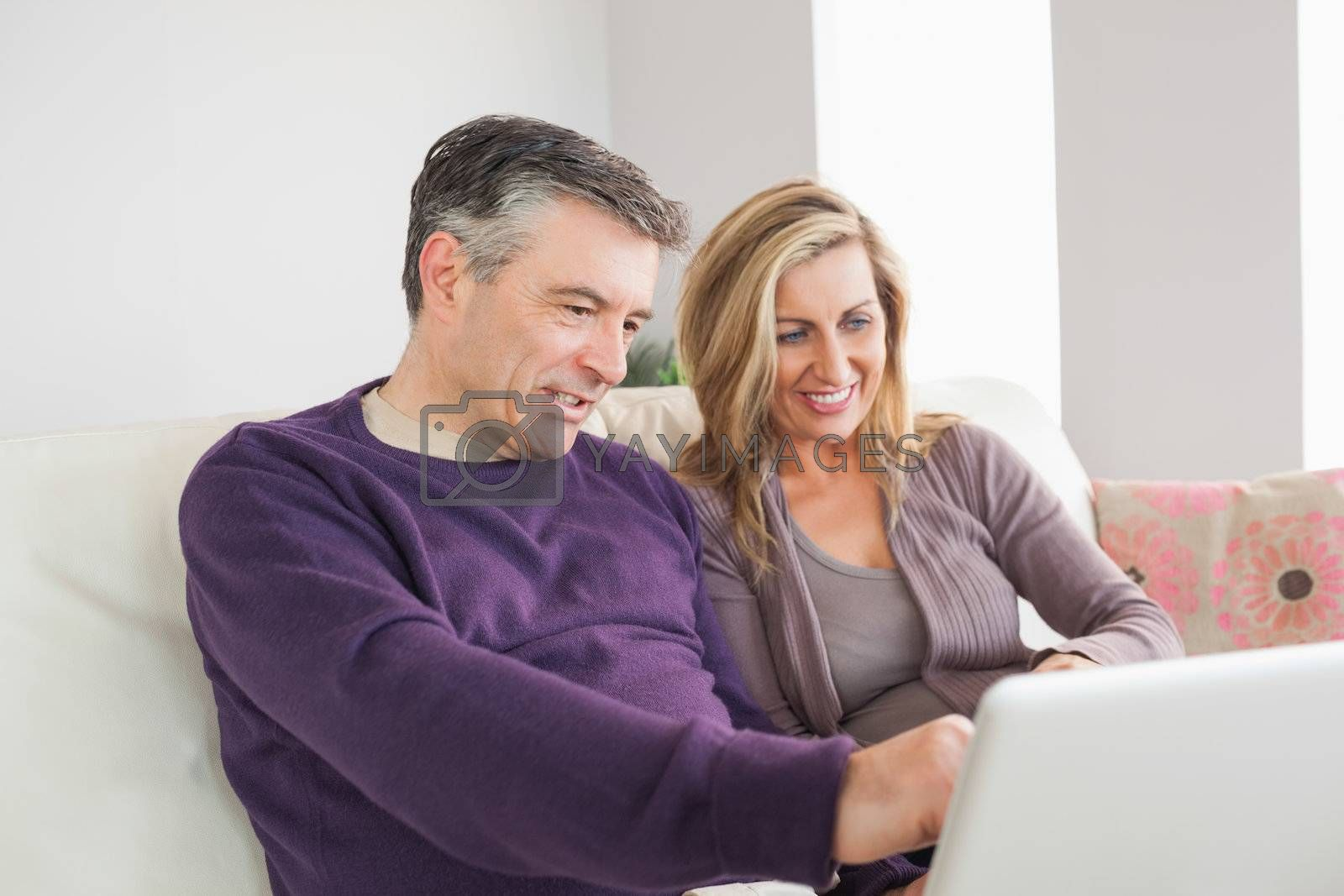 Happy couple watching their laptop by Wavebreakmedia